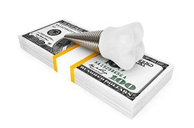 Model implant and money representing the cost of dental implants in Branford