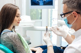 Dentist and patient discussing the cost of dental implants in Branford