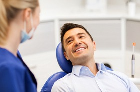 A middle-aged man lying in a dentist's chair smiling at the dentist