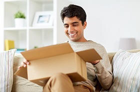 Man with healthy teeth and open box on lap